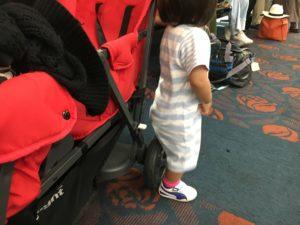 幼児がベビーカーの車輪に腰掛ける